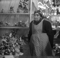 Mujer mapuche junto a artesanías de greda